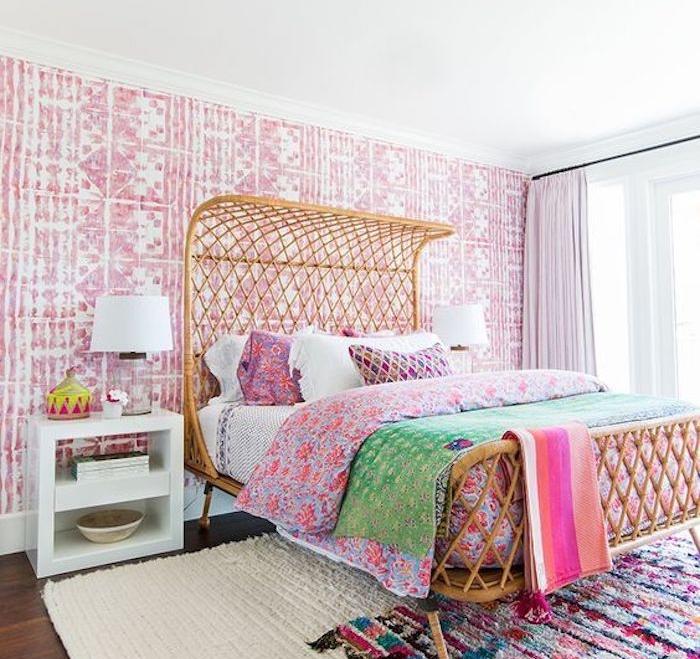 décoration chambre adulte avec papier peint oriental rose et blanc, lit exotique, linge de lit et tapis coloré, table de nuit blanche