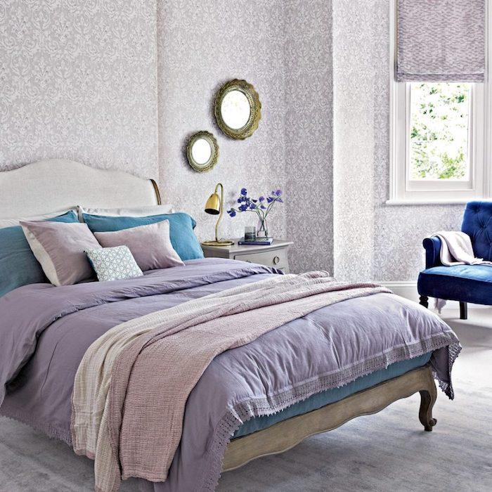 papier peint chambre adulte, motifs floraux gris sur un fond blanc, lit bois vintage, linge de lit violet, bleu et rose, fauteuil bleu marine