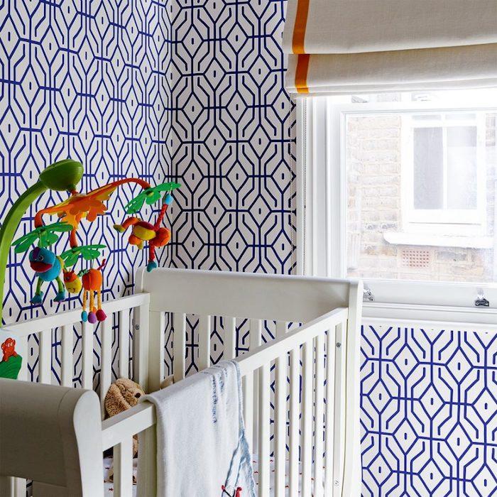 modele de papier peint géométrique, détails décortifs bleus sur un fond blanc, lit bébé blanc, jouets colorés