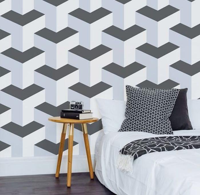 papier peint geometrique, formes blanc et gris, linge lit blanc et gris, table de nuit bois, appareil photo vintage