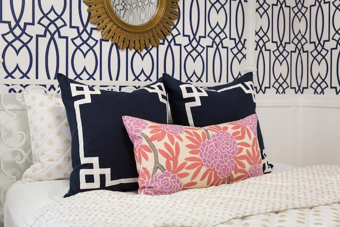 papier peint géométrique, motifs bleus sur un fond blanc, coussins bleu marine et à imprimé floral, linge de lit blanc, éléments dorés