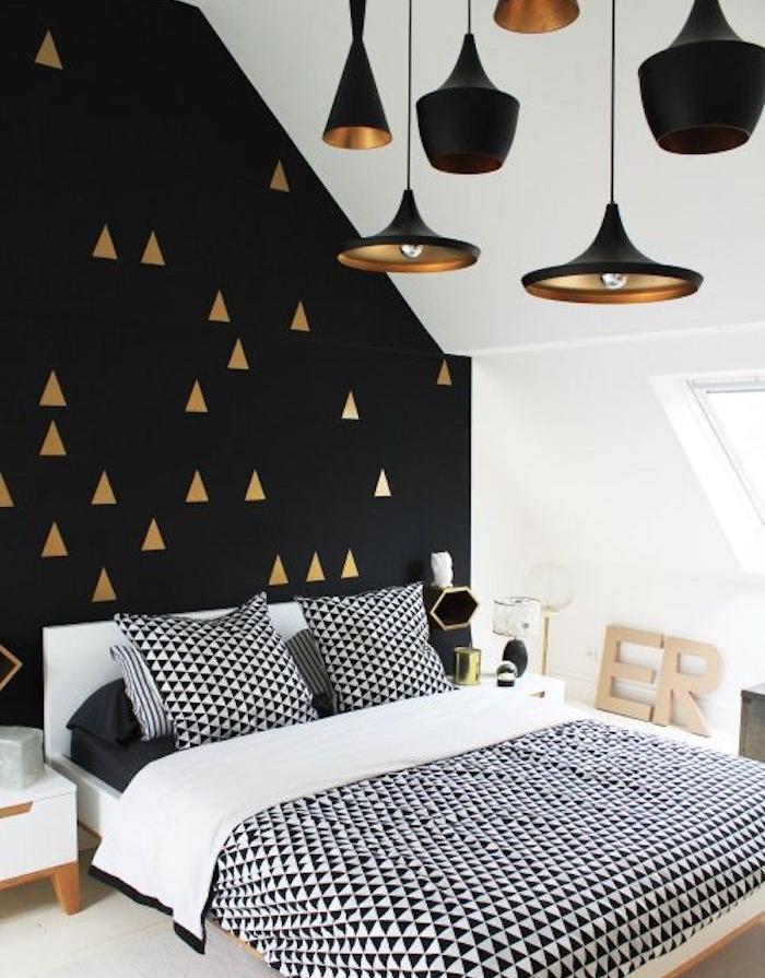 papier peint tendance style graphique, triangles couleur or sur un fond noir, linge de lit à triangles noires, suspensions noires
