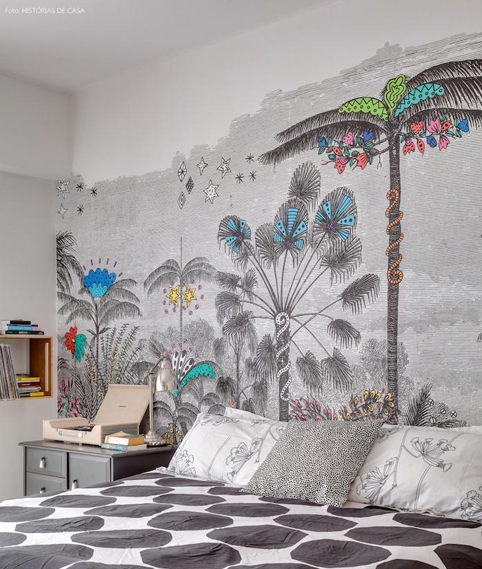 modele de papier peint graphique avec des touches de couleur, inspiration theme jungle, forêt tropical, linge de lit blanc et gris, table de nuit grise, étagère bois pour ranger des livres