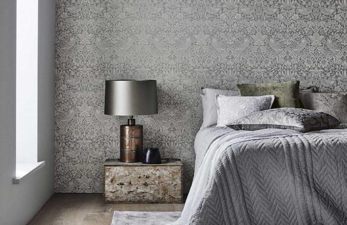 papier peint tendance gris et blanc, linge de lit gris, coussins gris et vert, parquet bois brut, table de nuit façon usé