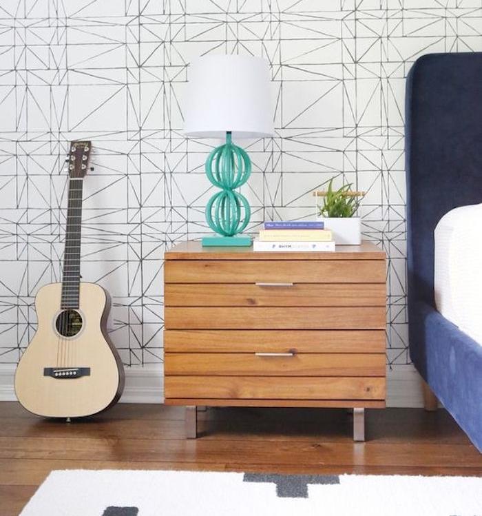 papier peint scandinave graphique, lignes noires sur fond blanc, commode bois, lit bleu marine. parquet marron, tapis blanc à crois gris, guitare classique
