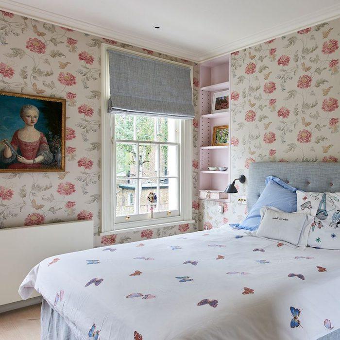papier peint vintage, roses rouges sur un fond blanc, linge de lit blanc avec imprimé papillon, tête de lit capitonnée, peinture cadre baroque