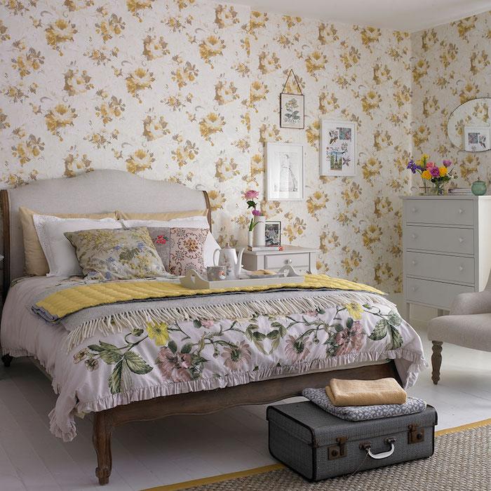 modele de papier peint vintage à imprimé floral, fleurs jaunes sur un fond blanc, lit bois, parquet clair, malle vintage gris en guise de bout de lit, coussins, couverture imprimé floral