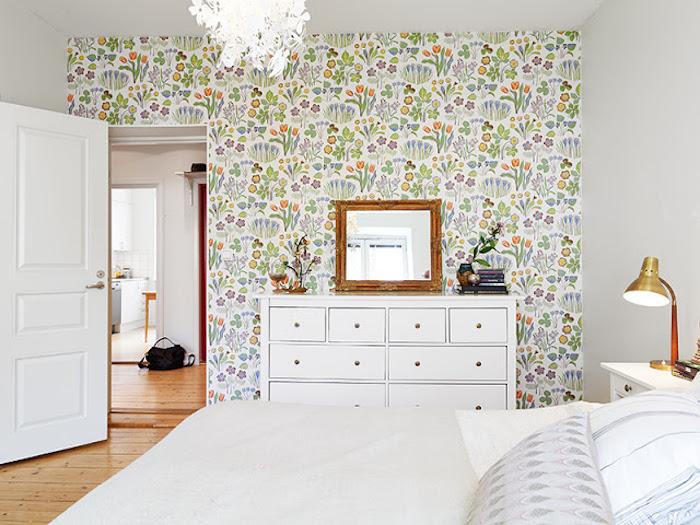 papier peint tendance à motifs floraux colorés, linge de lit blanc et gris, parquet clair, commode blanc, miroir dans un cadre bois vintage