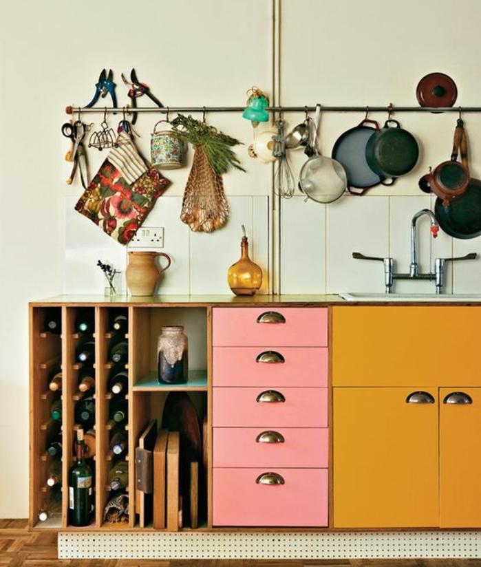 repeindre meuble cuisine, placards et tiroirs cuisine repeints en jaune ocre et rose pastel, rangement bouteilles à vin en bois et tube porte ustensil