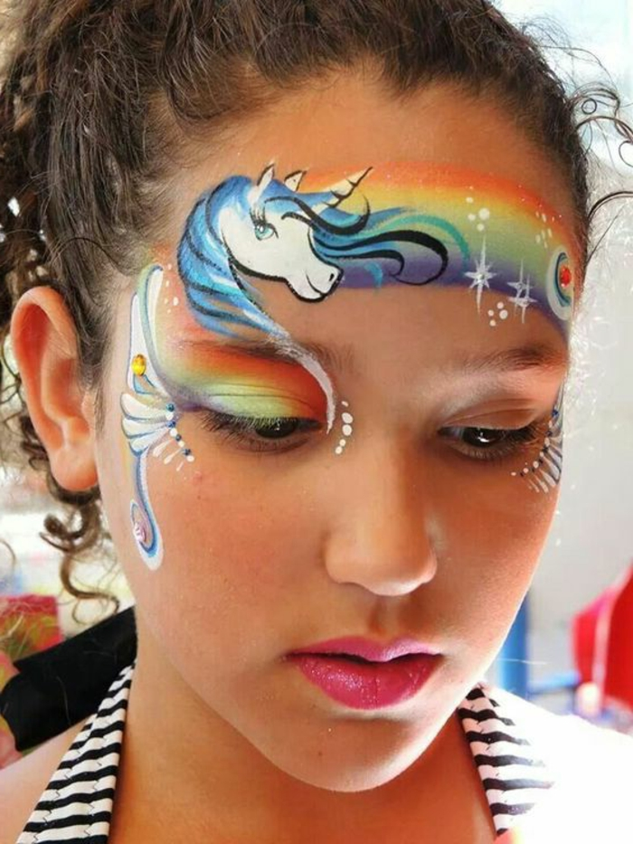 peinture visage, arc-en-ciel et licorne sur le visage d'une jeune fille