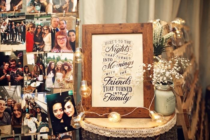 idee deco mariage, cadre en bois avec intérieur message, guirlande lumineuse et pele mele de photos sur une palette en bois, photographie mariés, amis