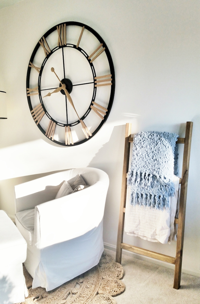 petite echelle en bois brut, rangement textiles, couvertures dans un salon scandinave, horloge vintage, canapé et table blancs