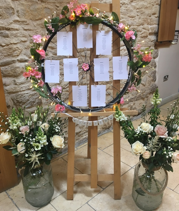 plan de table mariage original, style campagne chic, roue de bicyclette avec des étiquettes avec les noms des invités sur un chevalet et dame jeannes en verre, deco florale