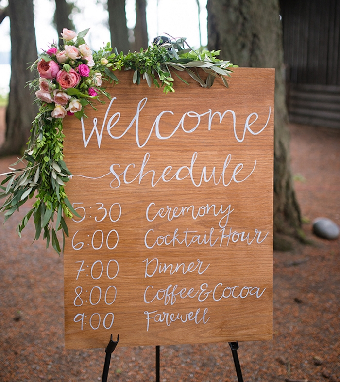 emploi du temps écrit sur un panneau en bois au feutre blanc, décoration de guirlande fleurie, diy mariage simple