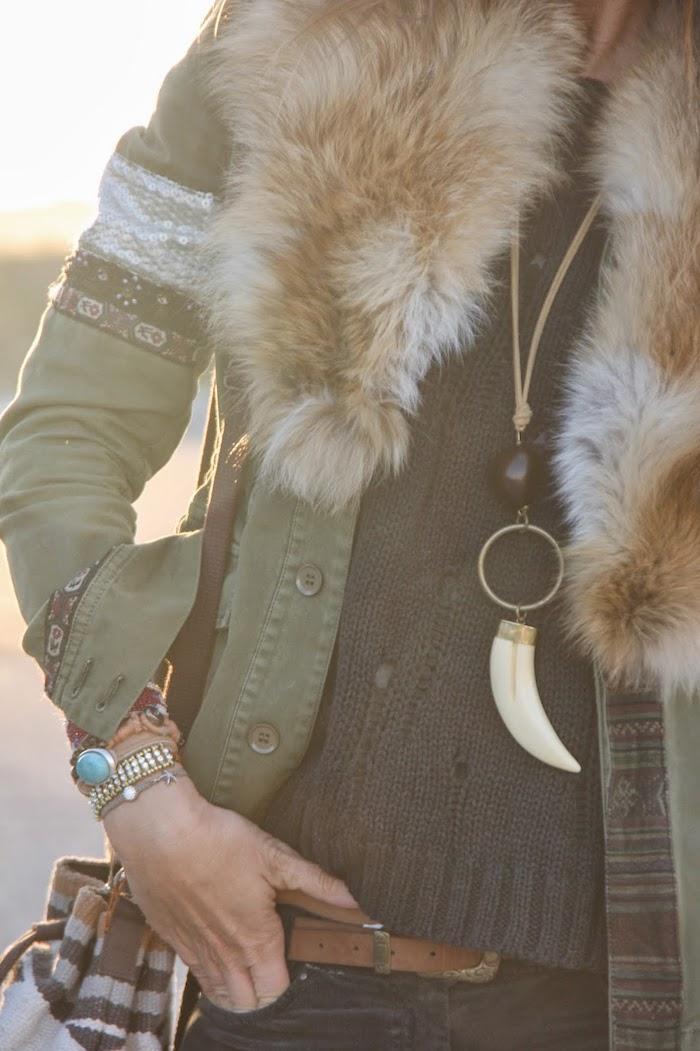 vetement boheme, sac à main en marron et gris, pantalon noir avec ceinture en cuir marron, veste kaki avec colle en faux fur