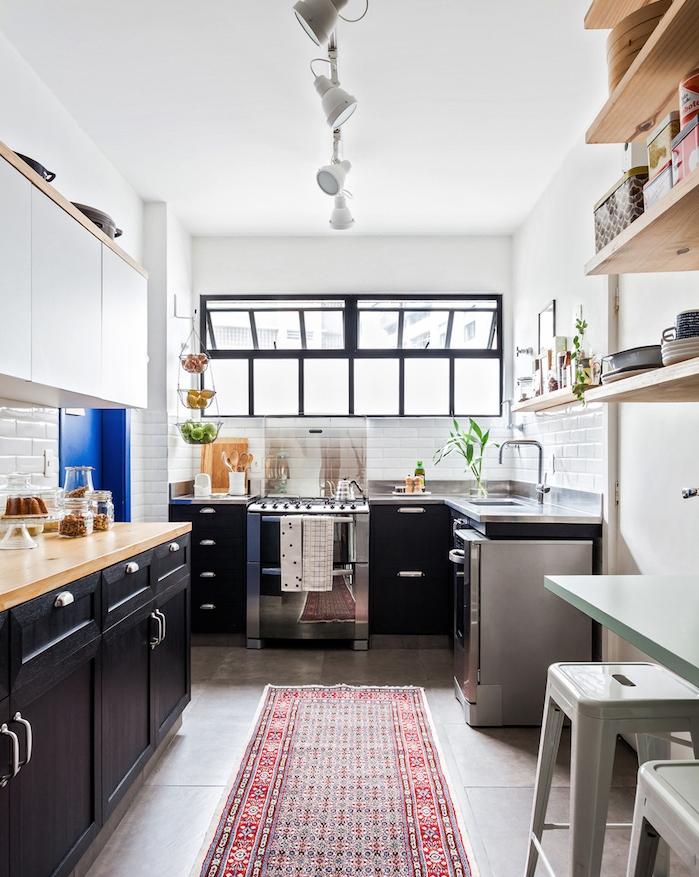 cuisine repeinte en noir et electromenagers en inox, idée de relooking cuisine, crédence blanche, étagères en bois, tapis oriental