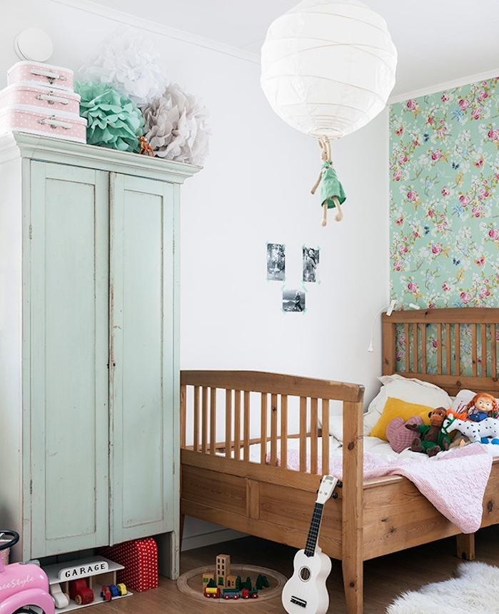 relooker armoire ancienne, peinture vert menthe, lit en bois, parquet clair, jouets et mur d accent en papier peint à motifs floraux, deco de fleurs en papier