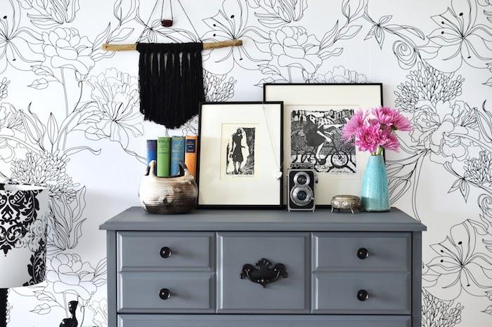 modele de papier peint graphique fleurs sur un fond blanc, commode gris, macramé noir, dessins graphiques, appareil photo vintage, livres
