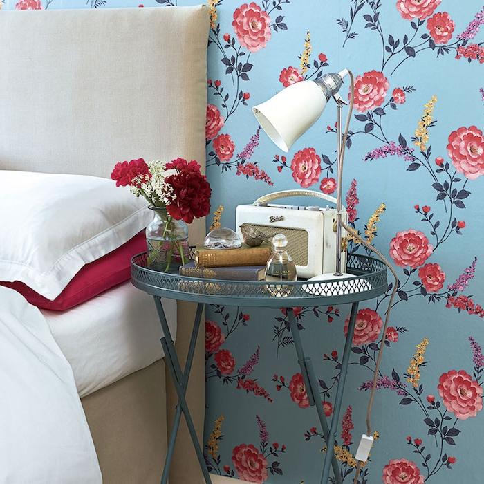 idée de papier peint vintage dans une chambre adulte, style shabby chic, roses rouges sur un fond bleu, table de nuit metallique bleu pastel, accessoires deco vintage