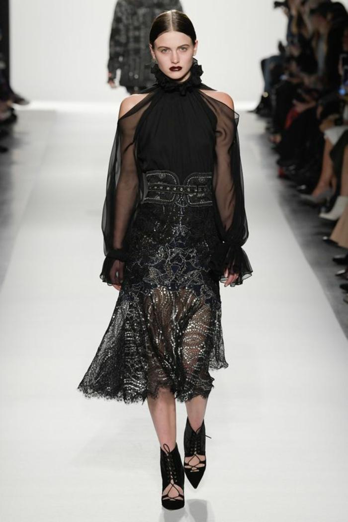 robe noire dentelle aux manches longues tombantes épaules dénudées bras en transparence et partie basse aux ornements en fil d argent