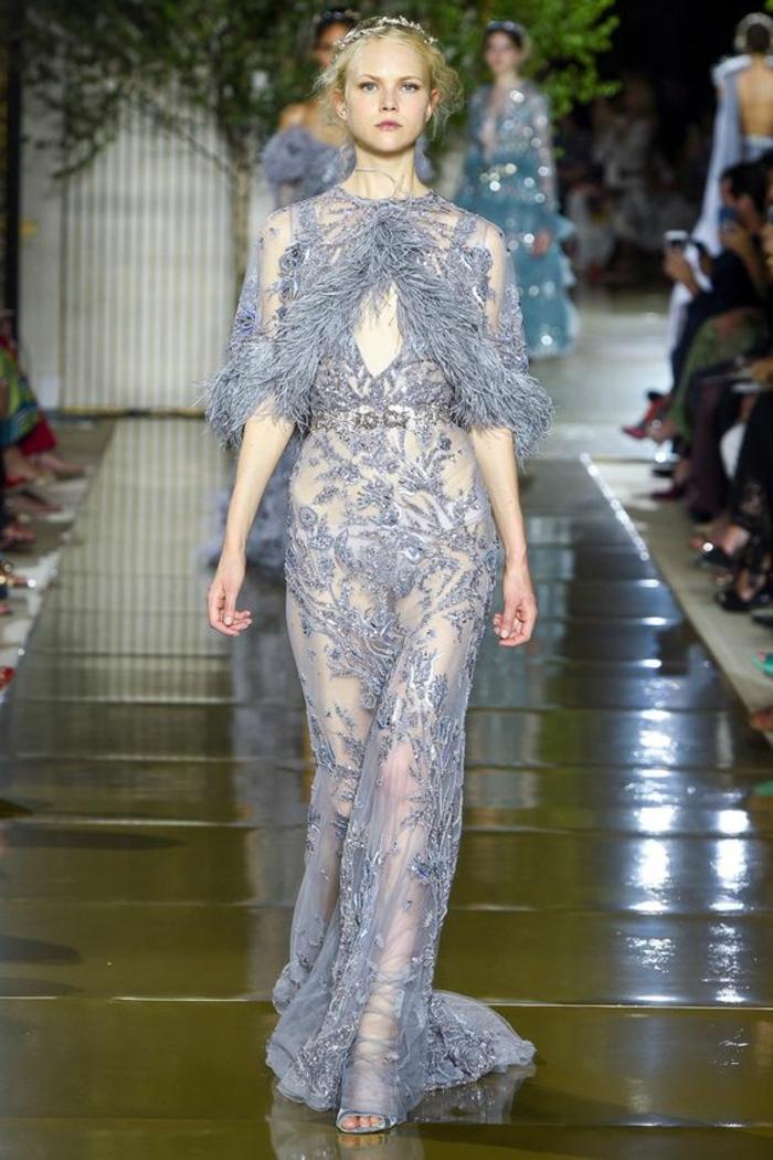 robe longue de soirée en bleu indigo avec des des plumes autour du décolleté et des manches longues jusqu'aux coudes