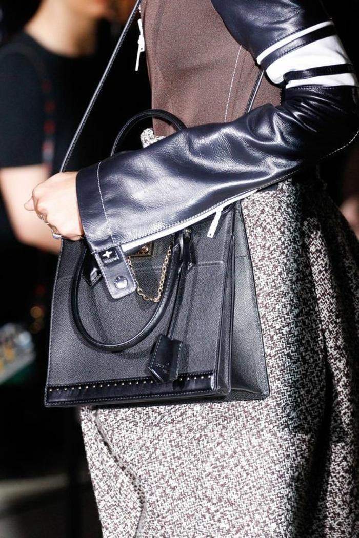 sac a dos vintage en noir en forme rectangulaire avec logo et petite chainette décorative en métal couleur argent création de Louis Vuitton