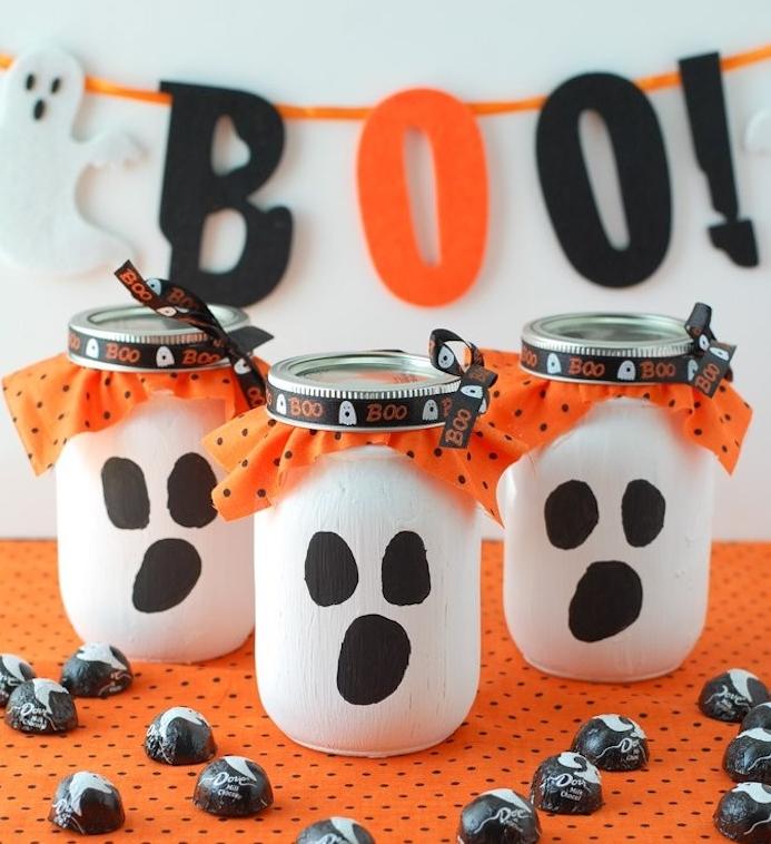 pots en verre transformés en boites a bonbons, peinture blanche et taches noirs pour bouche et oreilles et petite mouchoir orange sous le couvercle, activite manuelle halloween