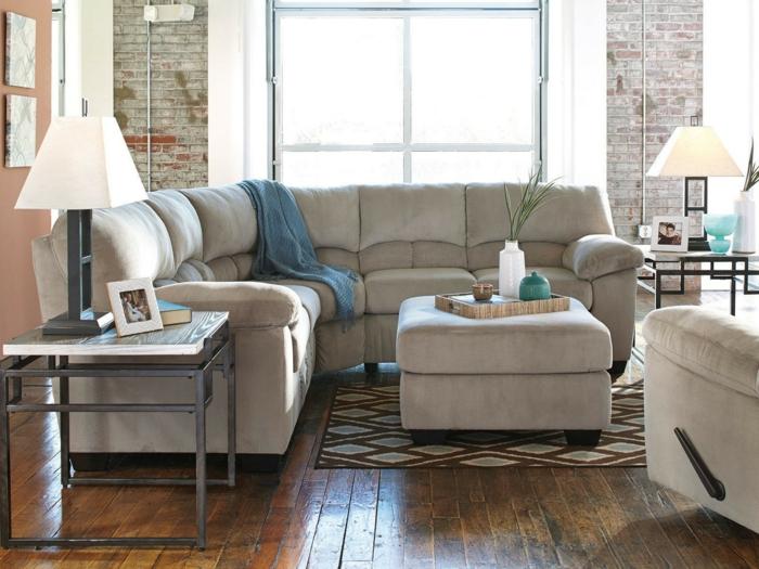 salon cocooning, grand sofa d'angle, sol en bois, murs en briques, table industrielle et lampe abat-jour