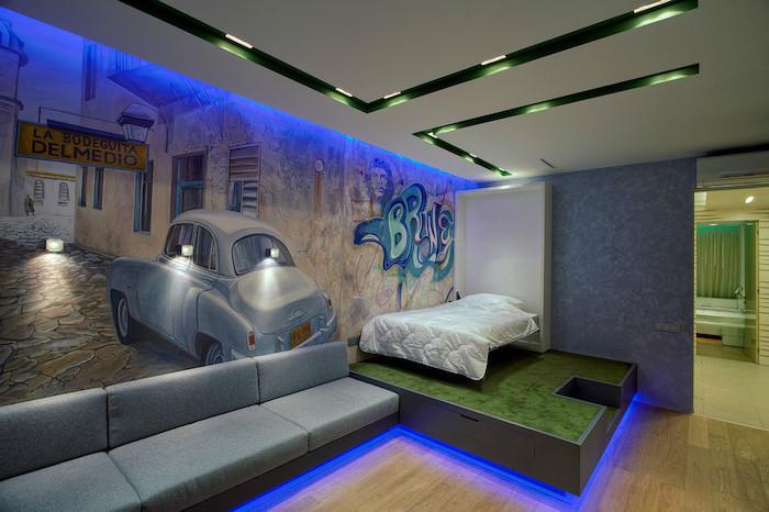 chambre ado garçon, canapé en tissu gris et lit en bois, éclairage néon bleu sol et plafond, plafond suspendu en blanc