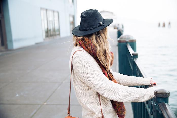 pull en laine, balayage blond sur cheveux longs bouclés, sac à main en cuir marron avec écharpe longue à motifs floraux