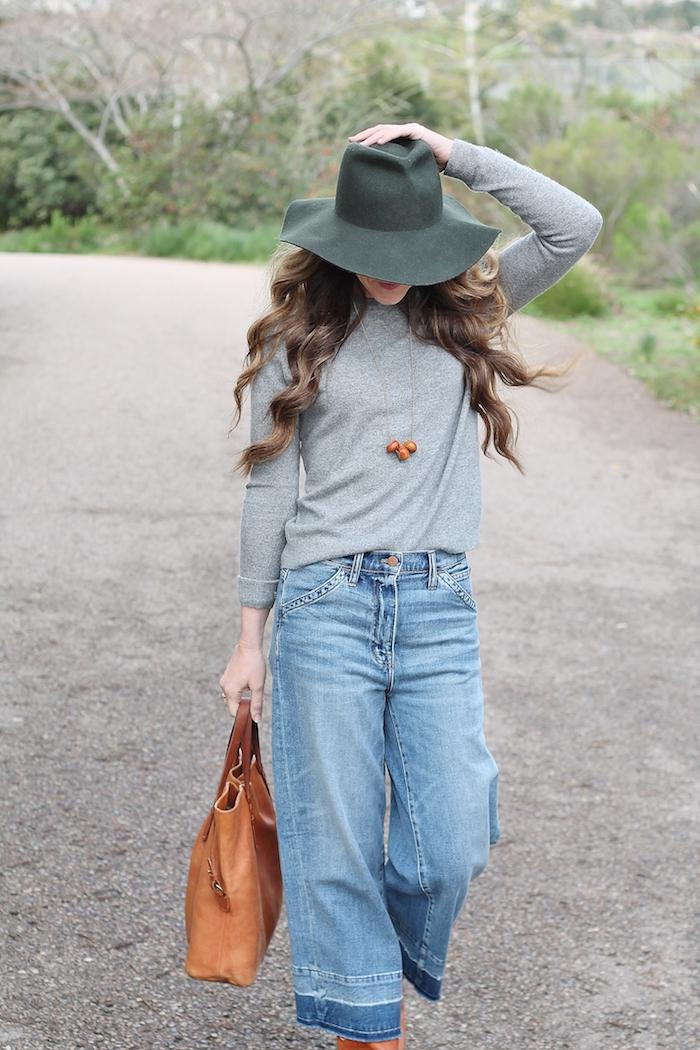 coupe de cheveux longs femme, tenue avec pantalon en denim clair et blouse grise, sac à main marron