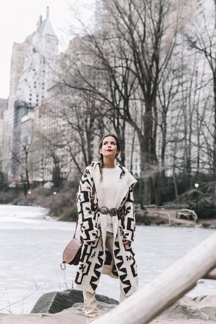 pull en laine, coiffure cheveux longs en tresse sur le côté, maquillage lèvres rouges, manteau long en blanc avec motifs géométriques noirs