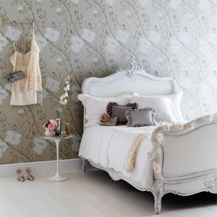 papier peint vintage et lit baroque dans une chambre design feminine, coussins gris sur un linge blanc, parquet blanchi, revetement mur motifs floraux sur un fond gris