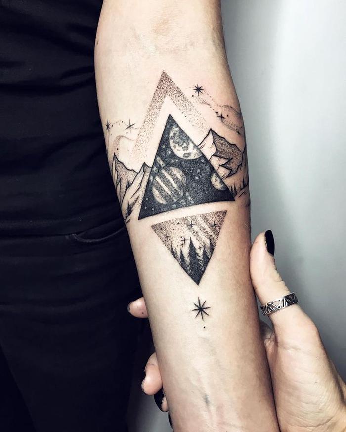 un tatouage geometrique représentant la terre et le cosmos dans deux triangles opposés