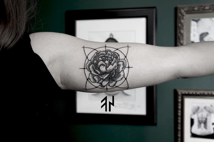 tatouage cercle parfait avec une jolie rose à l'intérieur réalisé sur le biceps