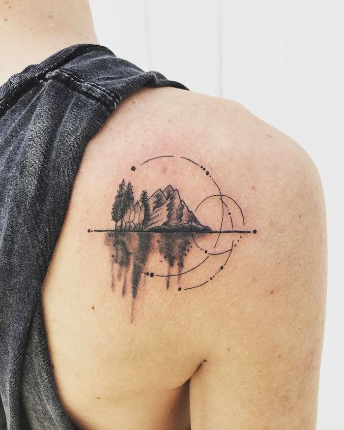 un tatouage cercle interrompu associé à un paysage montagnard graphique à effet miroir