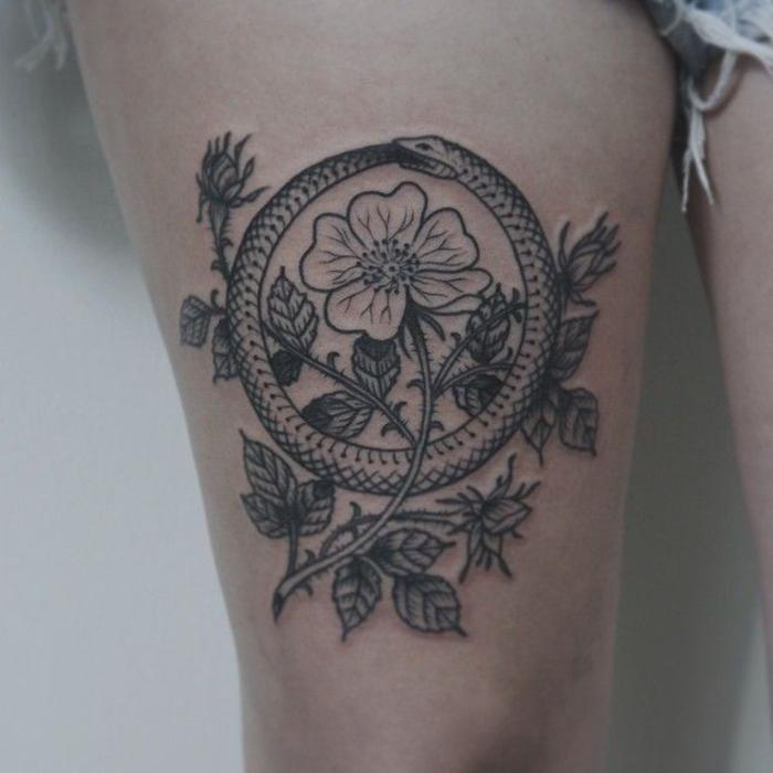 un tatouage cercle symbolique représentant un serpent qui se mord la queue entremêlée de motifs naturels