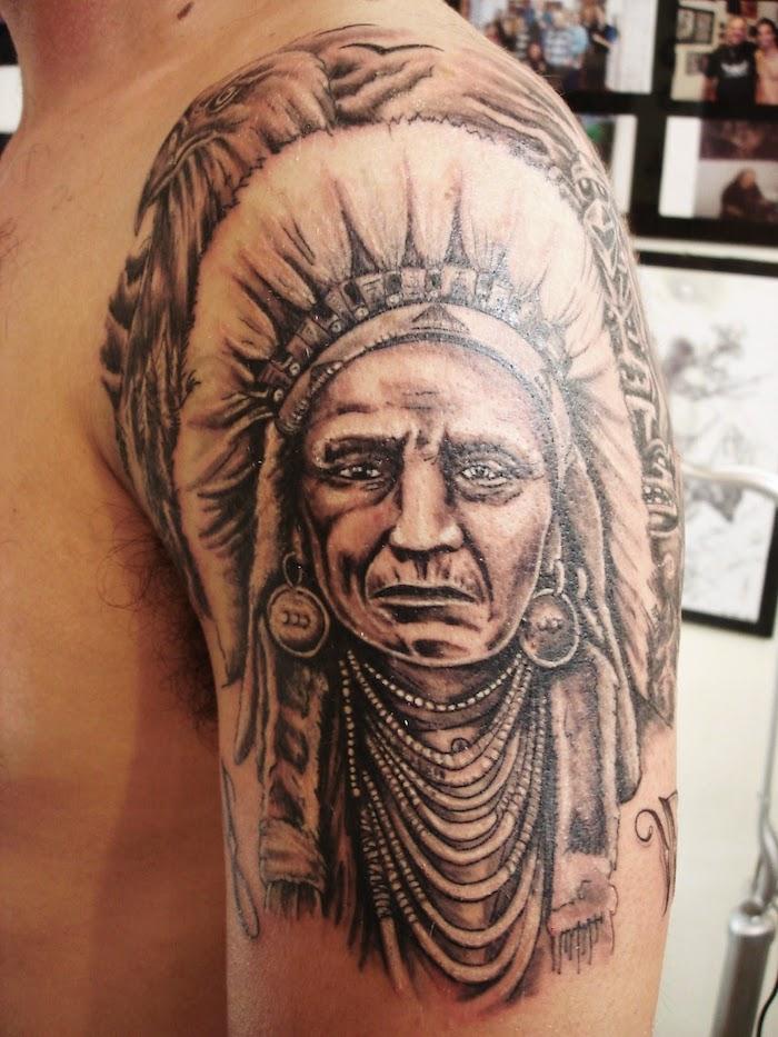 motif amérindien, tatouage sur bras et épaule pour homme, dessin en encre tête autochtone avec plumes