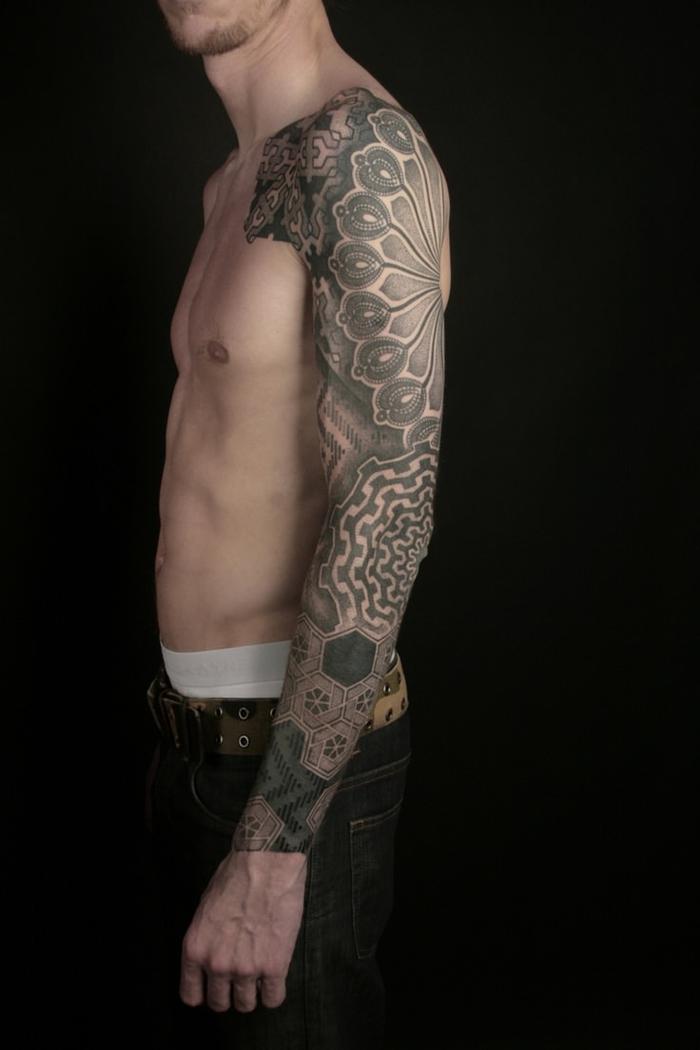 un tatouage homme bras entier au design graphique complexe réunissant des motifs floraux et des formes géométriqies