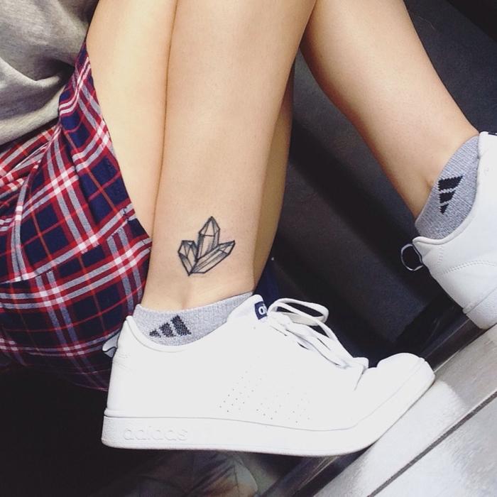 un tatouage simple dans l'esprit minimaliste représentant trois cristaux sur la cheville