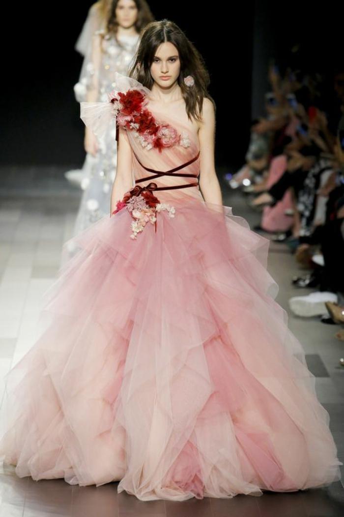 robe de soirée longue en rose poudré avec des grandes fleurs en tissu rouge autour du décolleté et autour de la taille