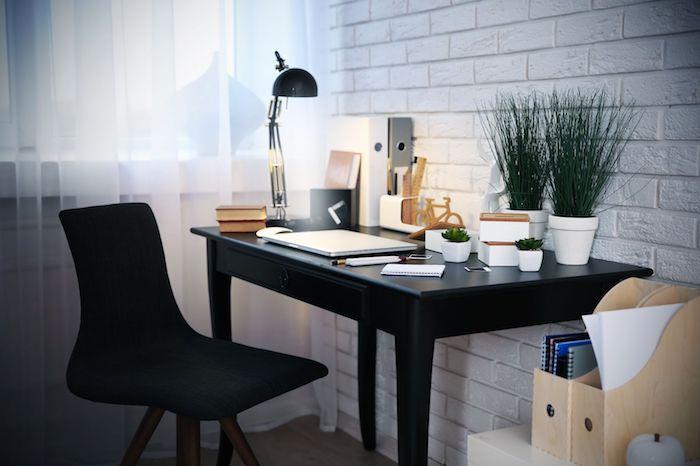 bureau avec plan de travail, office aux murs en briques blanches, classeurs de papier à imitation bois clair