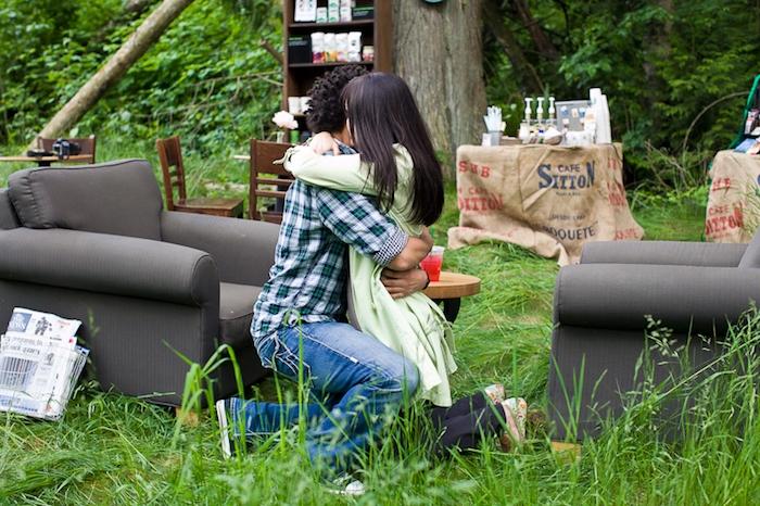 un café en plein air et un copain qui sert une surprise inattendue, fauteuils et table basse sur un gazon, demande en mariage originale