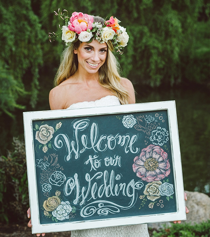 tableau noir avec bienvenue écrit dessus et des dessins de fleurs sur un tableau noir, couronne de fleurs sur la tête d une femme