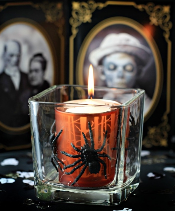 bougie dans un petit verre avec es araignées artificielles et fond de photographies en noir et blanc effrayants dans des cadres baroques