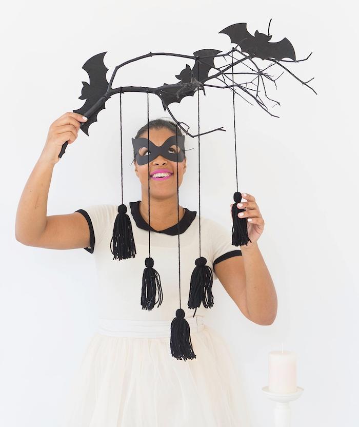 branche en bois, repeint en noir avec des pompons à franges noirs et des silhouettes de chauve souris, deco halloween a faire soi meme