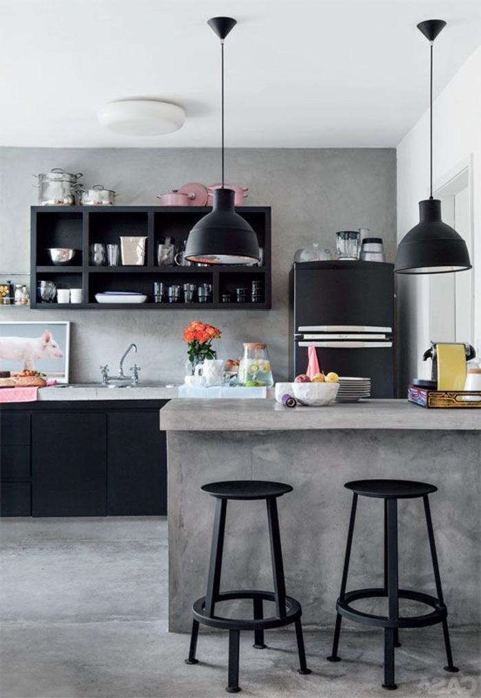 la finition noire mats des meubles industriels s'associent parfaitement à l'aspect brut de l'îlot de cuisine en béton