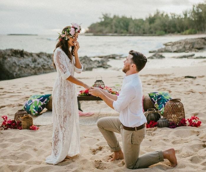 une demande en mariage romantique sur une plage couverte de sable, coussins colorés, couverture pour s asseoir, decoration de lanternes et fleurs rouges