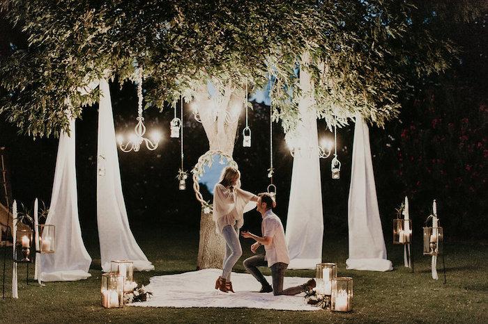 idée de demande en mariage romantique sur un pré dans la forêt, décoration de miroir, voiles blanches, lanternes avec bougies, lustres élégantes