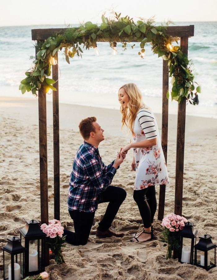 une demande en mariage de rêve sur une plage, arche fleurie en bois, plusieurs lanternes noires et bouquets de fleurs